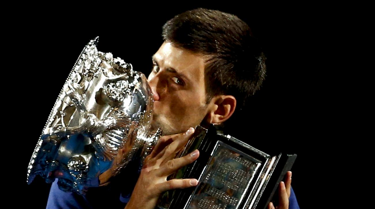 Novak Djokovic of Serbia kisses his trophy after defeating Andy Murray of Britain in the men's singles final at the Australian Open tennis championships in Melbourne, Australia, Sunday, Jan. 31, 2016.(AP Photo/Rafiq Maqbool)