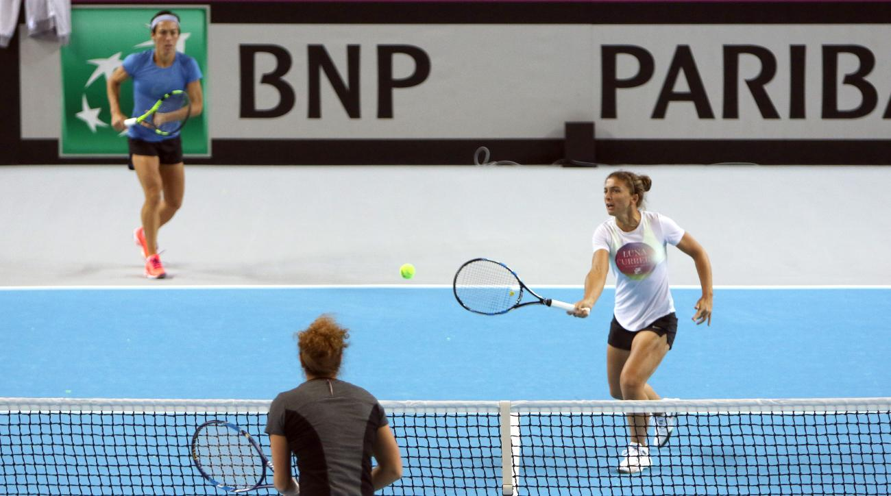 Italy's Sara Errani, right,  returns the ball to Martina Caregaro , watched by  Francesca Schiavone , left, during a training session for the Fed Cup competition in Marseille, southern France, Thursday, Feb.4, 2016. France will face Italy on Feb.6-7 in th