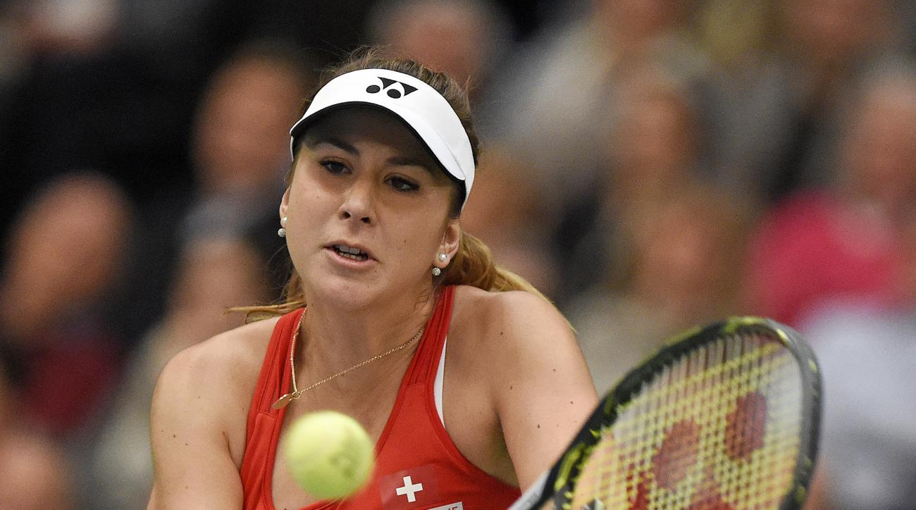 Belinda Bencic of Switzerland returns a ball to Andrea Petkovic of Germany during the Fed Cup World Group first round tennis match between Germany and Switzerland in Leipzig, Germany, Saturday, Feb. 6, 2016. (AP Photo/Jens Meyer)