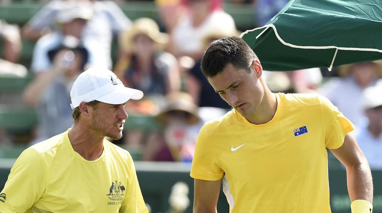 Australia's coach, Lleyton Hewitt, left talks to Bernard Tomic, right, while playing against United States' Jack Sock during their Davis Cup singles match in Melbourne, Australia, Friday, March 4, 2016. (AP Photo/Andrew Brownbill)