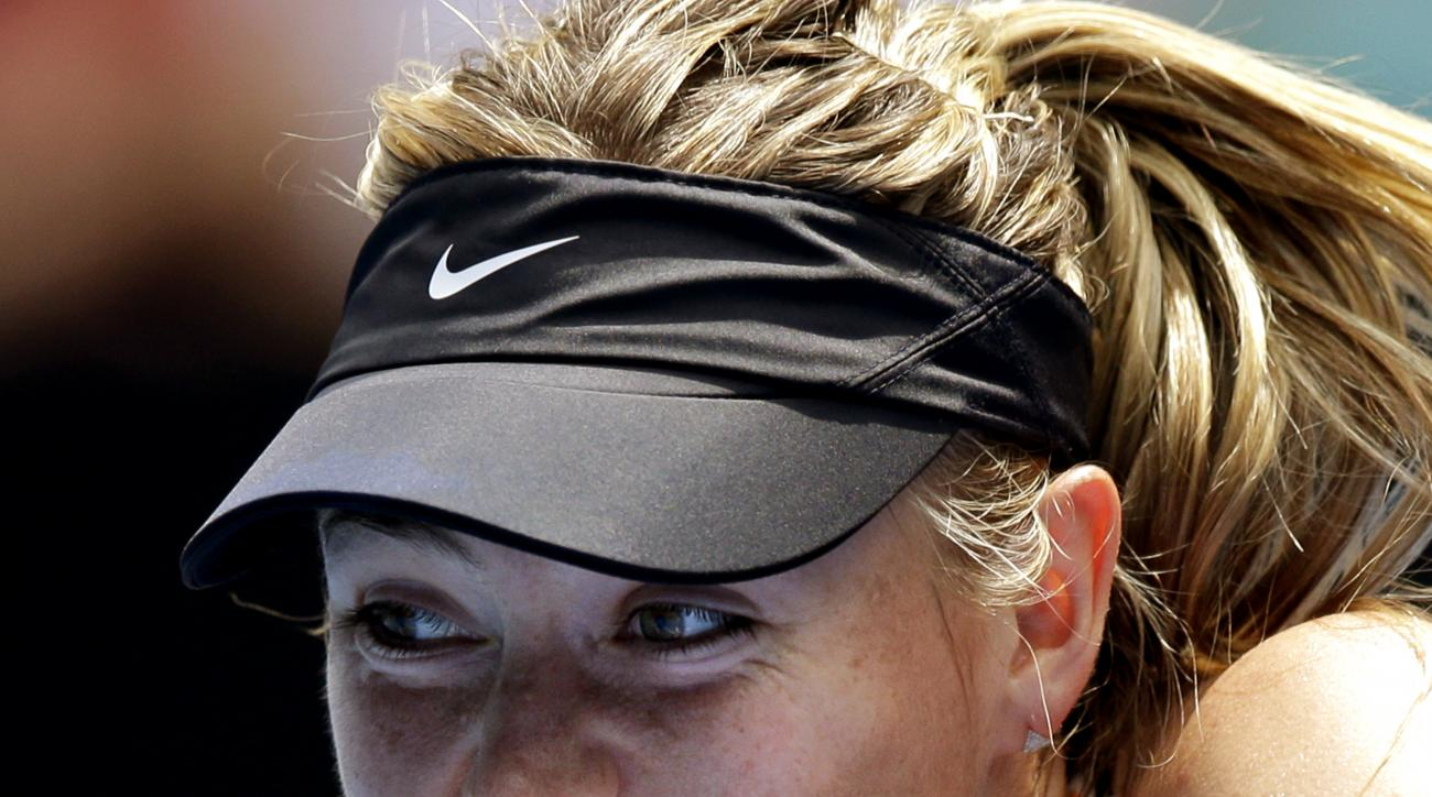 FILE - In this Jan. 26, 2016, file photo, Maria Sharapova of Russia plays a backhand return to Serena Williams of the United States during their quarterfinal match at the Australian Open tennis championships in Melbourne, Australia. Three of Maria Sharapo