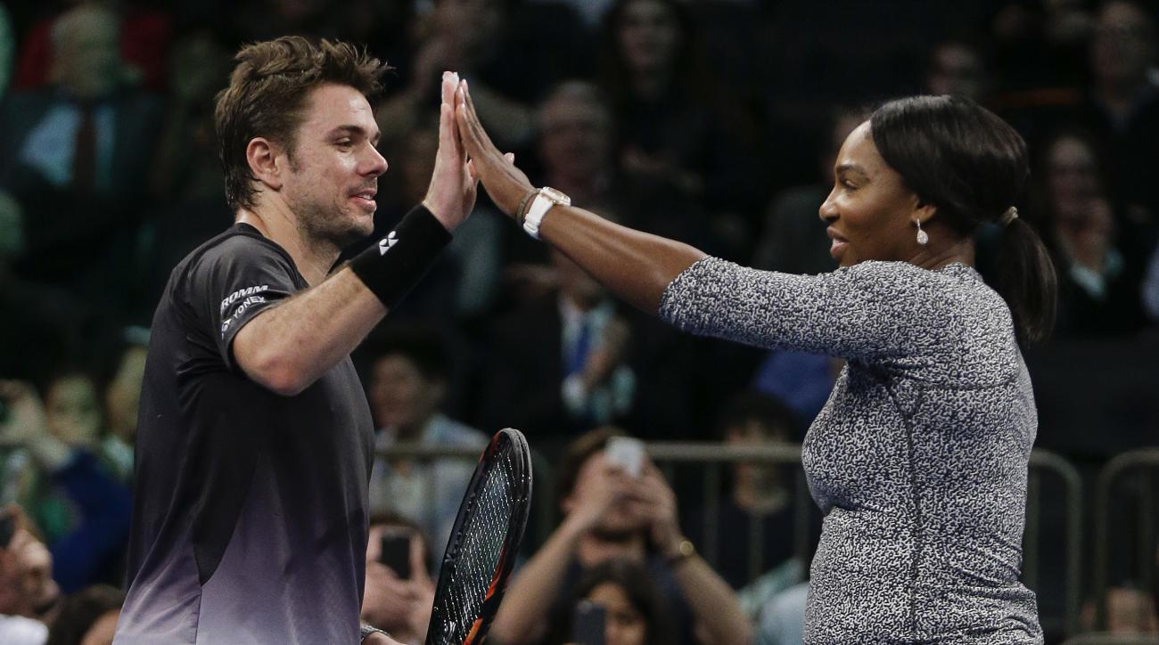 Stanislas Wawrinka, left, high-fives Serena Williams while playing an impromptu game of doubles against Caroline Wozniacki and Gael Monfils during the BNP Paribas Showdown tennis exhibition, Tuesday, March 8, 2016, in New York. (AP Photo/Julie Jacobson)