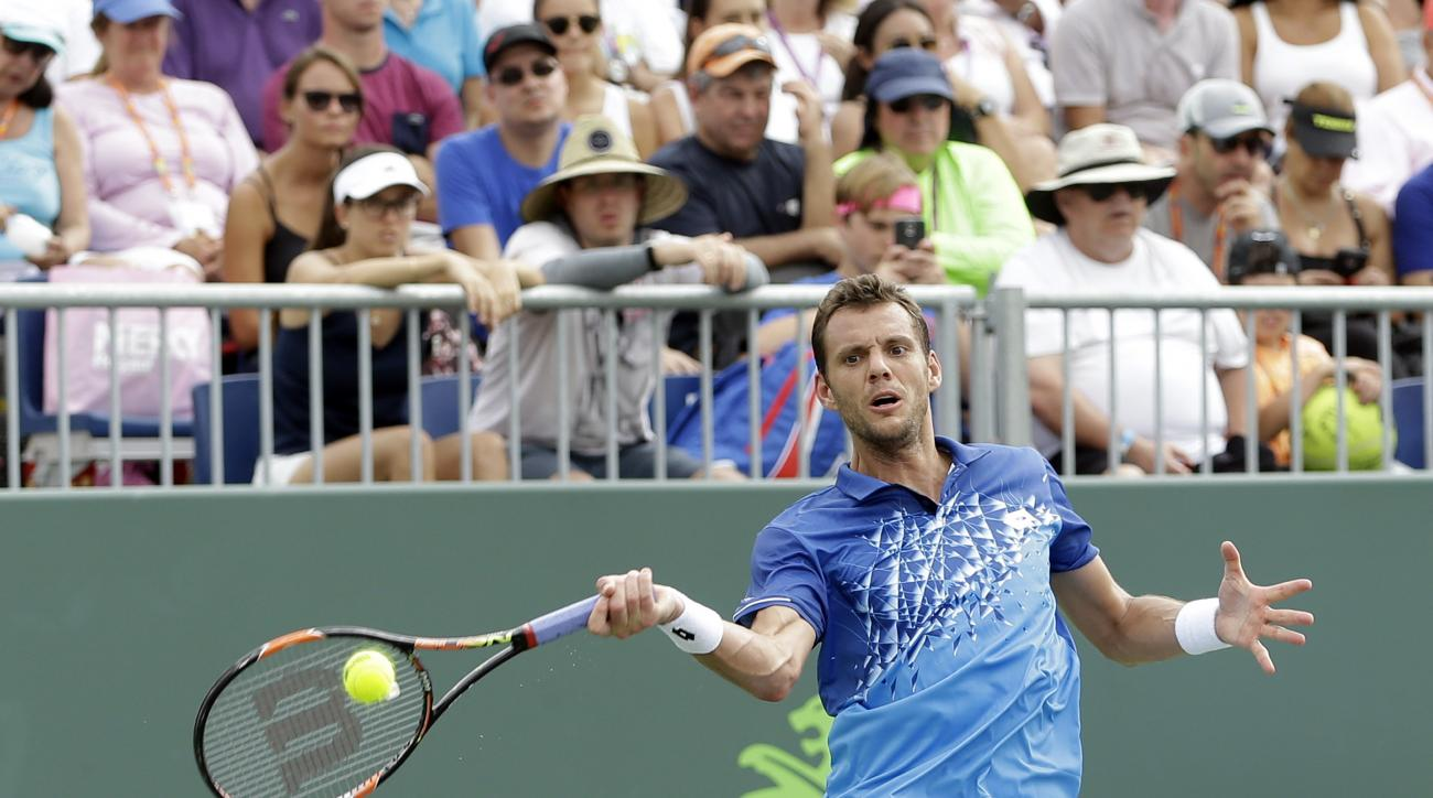 Paul-Henri Mathieu, of France, returns to Santiago Giraldo, of Colombia, during a match at the Miami Open tennis tournament in Key Biscayne, Fla., Thursday, March 24, 2016. (AP Photo/Alan Diaz)
