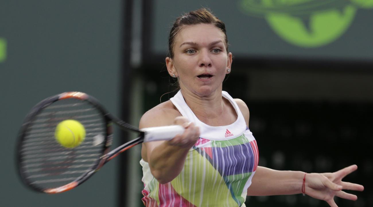 Simona Halep, of Romania, returns to Timea Bacsinszky during their match at the Miami Open tennis tournament, Tuesday, March 29, 2016, in Key Biscayne, Fla.  Bacsinszky won 4-6, 6-3, 6-2. (AP Photo/Lynne Sladky)
