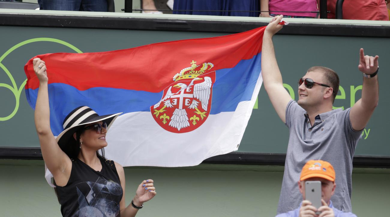 Fans wave a Serbian flag during the men's singles final match between Novak Djokovic and Kei Nishikori at the Miami Open tennis tournament, Sunday, April 3, 2016, in Key Biscayne, Fla. Djokovic won 6-3, 6-3. (AP Photo/Lynne Sladky)