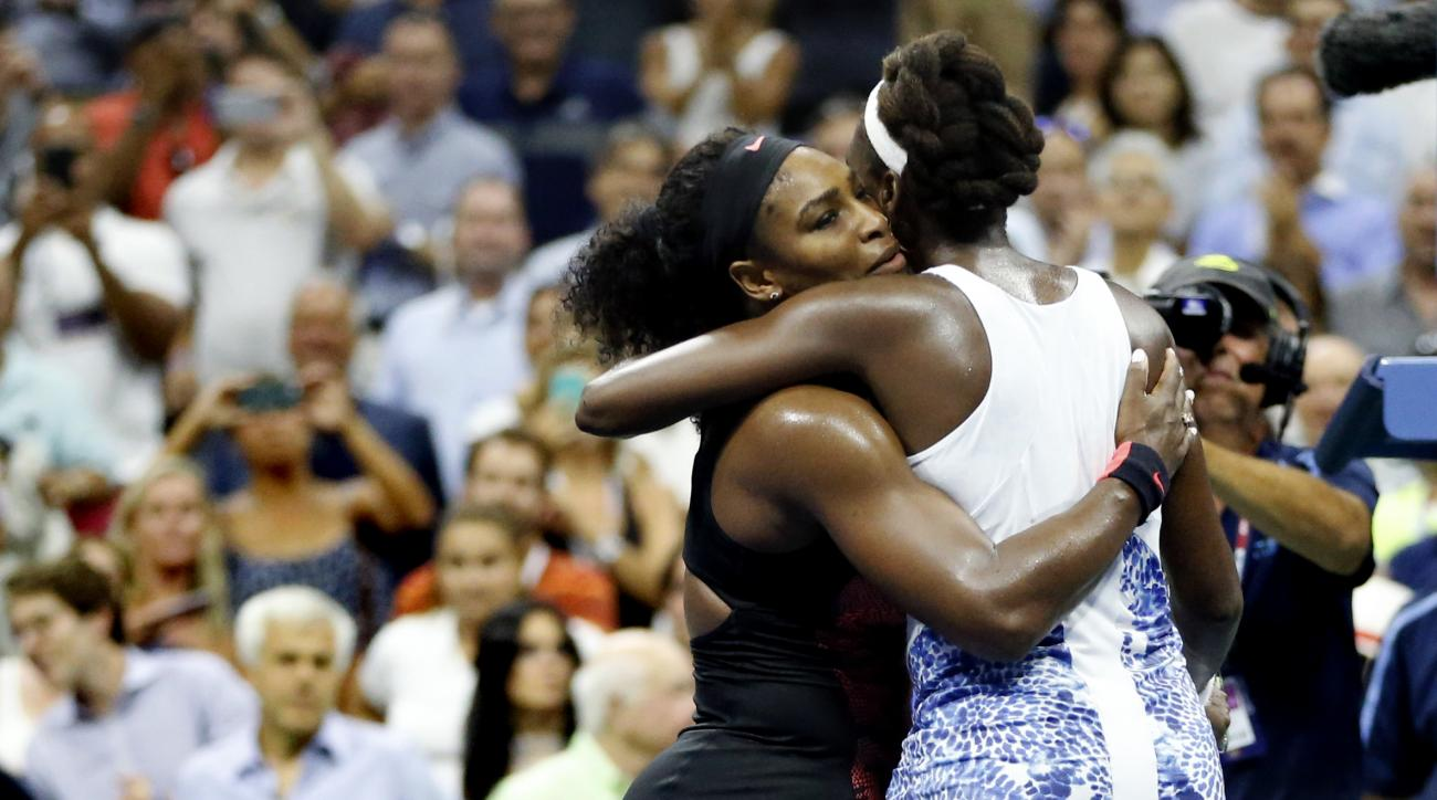Serena Williams, left, hugs Venus Williams after winning their quarterfinal match at the U.S. Open tennis tournament, Tuesday, Sept. 8, 2015, in New York. (AP Photo/Julio Cortez)