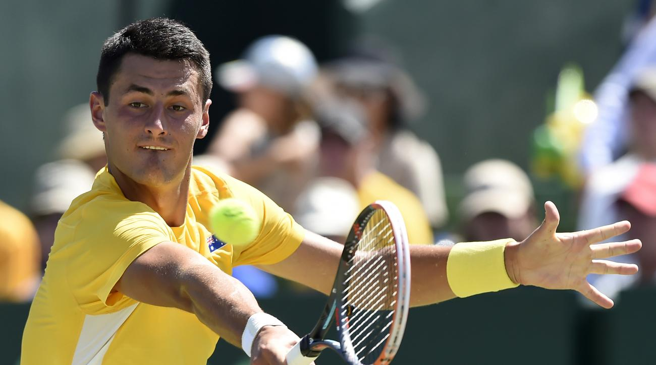 Australia's Bernard Tomic makes a backhand return to  United States' Jack Sock during their Davis Cup singles match in Melbourne, Australia, Friday, March 4, 2016.(AP Photo/Andrew Brownbill)