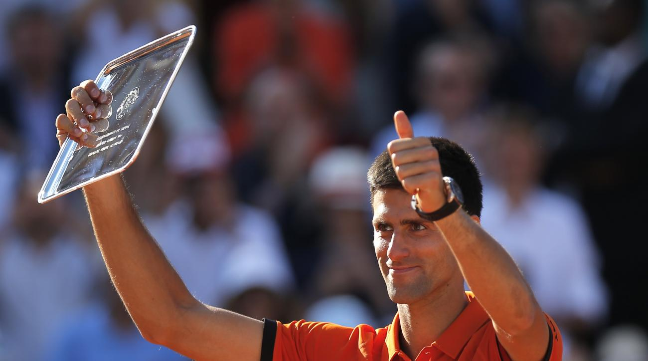 FILE - In this June 7, 2015, file photo, Serbia's Novak Djokovic shows his second place plate after losing to Switzerland's Stan Wawrinka in the final match of the French Open tennis tournament at the Roland Garros stadium in Paris. The French Open begins