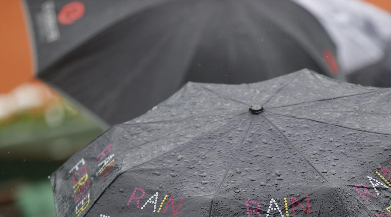 "Spectators sit under an umbrella reading ""Rain Forever"" shortly before all first round matches of the French Open tennis tournament were delayed till the next day because of the rain at Roland Garros stadium in Paris, France, Sunday, May 22, 2016. (AP Pho"
