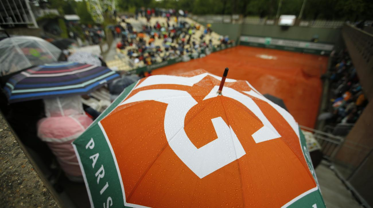 Spectators wait at covered tennis courts for the start of rain delayed first round matches of the French Open tennis tournament against at Roland Garros stadium in Paris, France, Monday, May 23, 2016. Showers over Paris on Monday have forced the organizer