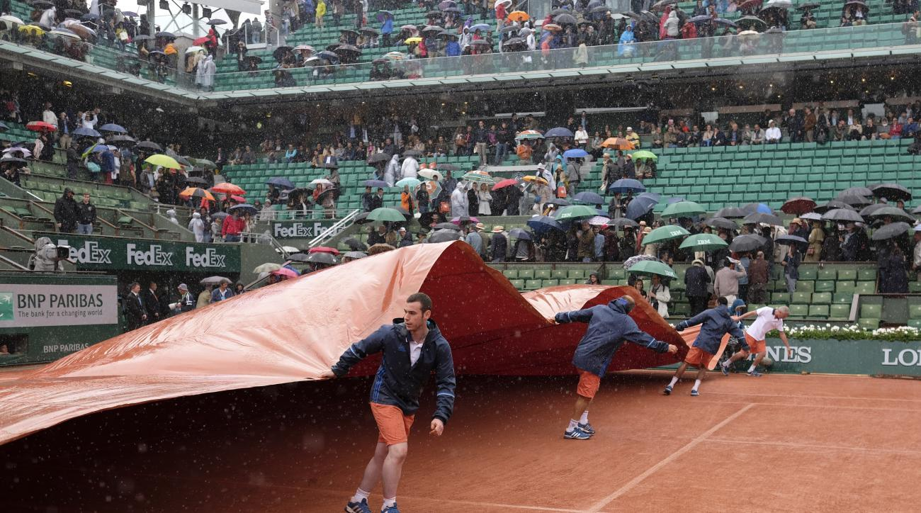 Stadium workers cover the clay court as the fourth round match of the French Open tennis tournament between Japan's Kei Nishikori and France's Richard Gasquet was interrupted because of the rain at the Roland Garros stadium in Paris, France, Sunday, May 2