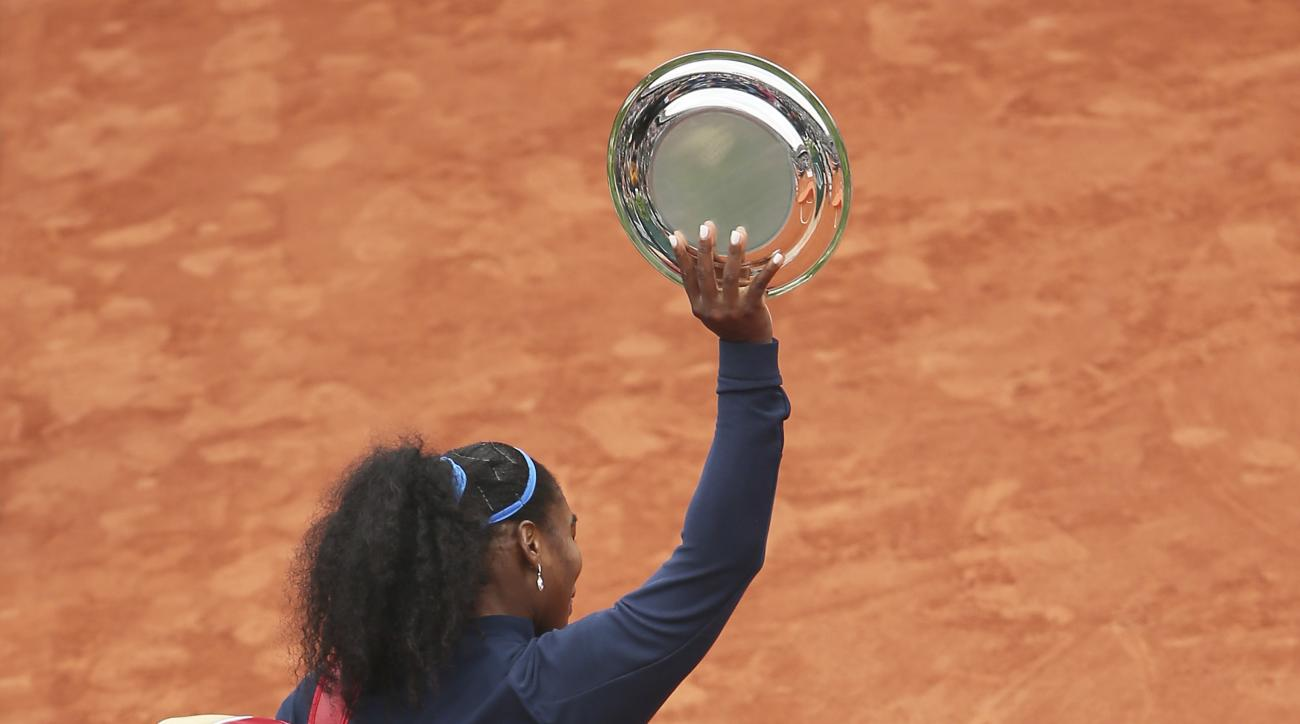 Serena Williams of the U.S. holds the runner-up trophy as she leaves after losing the final of the French Open tennis tournament against Spain's Garbine Muguruza in two sets 7-5, 6-4, at the Roland Garros stadium in Paris, France, Saturday, June 4, 2016.