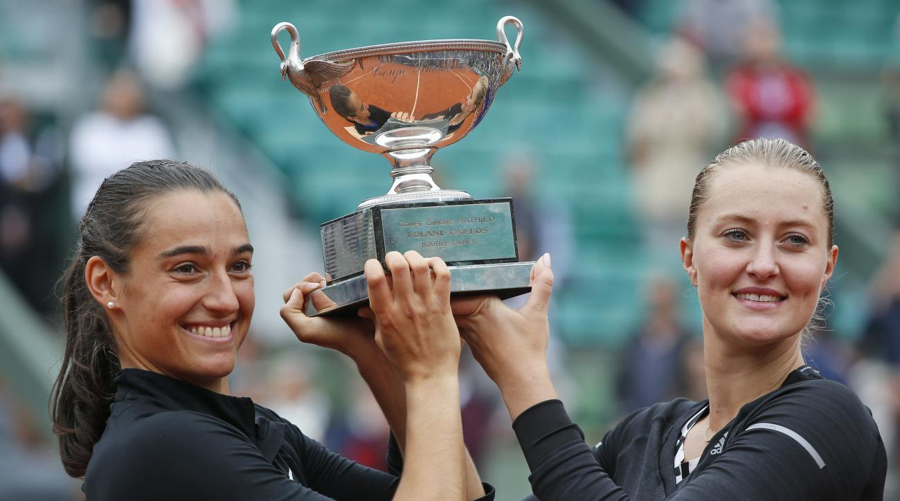 Caroline Garcia, left, and Kristina Mladenovic of France celebrate with the trophy after winning the women's doubles final of the French Open tennis tournament against Ekaterina Makarova and Elena Vesnina of Russia in three sets 6-3, 2-6, 6-4, at the Rola