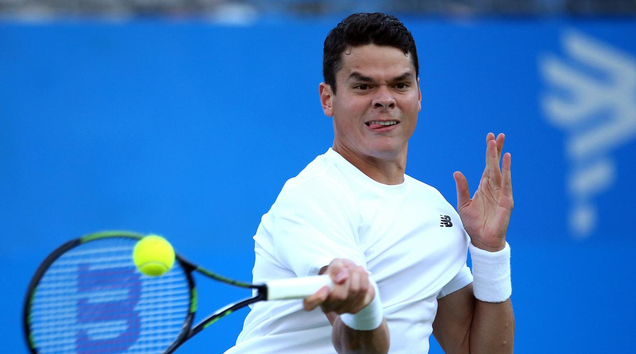 Canada's Milos Raonic returns the ball to Australia's Nick Kyrgios on day two of the Queen's grass-court tennis tournament in London, Tuesday June 14, 2016. (Steve Paston/PA via AP) UNITED KINGDOM OUT NO SALES NO ARCHIVE