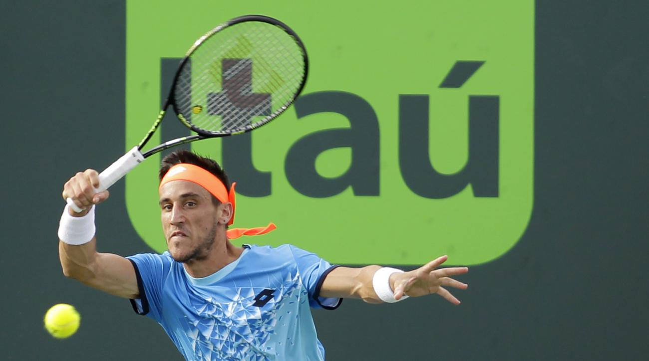 Damir Dzumhur, of Bosnia, returns the ball to Milos Raonic, of Canada, during the Miami Open tennis tournament, Tuesday, March 29, 2016, in Key Biscayne, Fla. (AP Photo/Luis M. Alvarez)