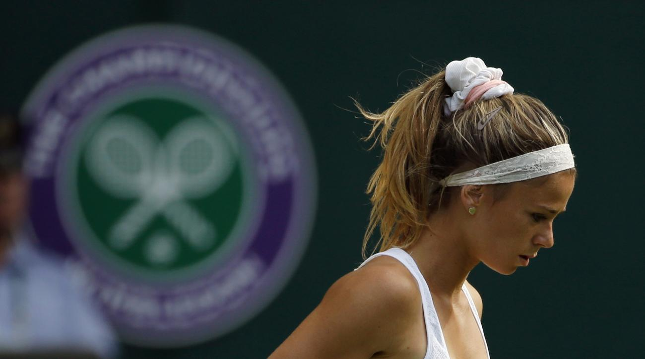 Camila Giorgi of Italy reacts after winning the second set against Garbine Muguruza of Spain during their women's singles match on day one of the Wimbledon Tennis Championships in London, Monday, June 27, 2016. (AP Photo/Alastair Grant)