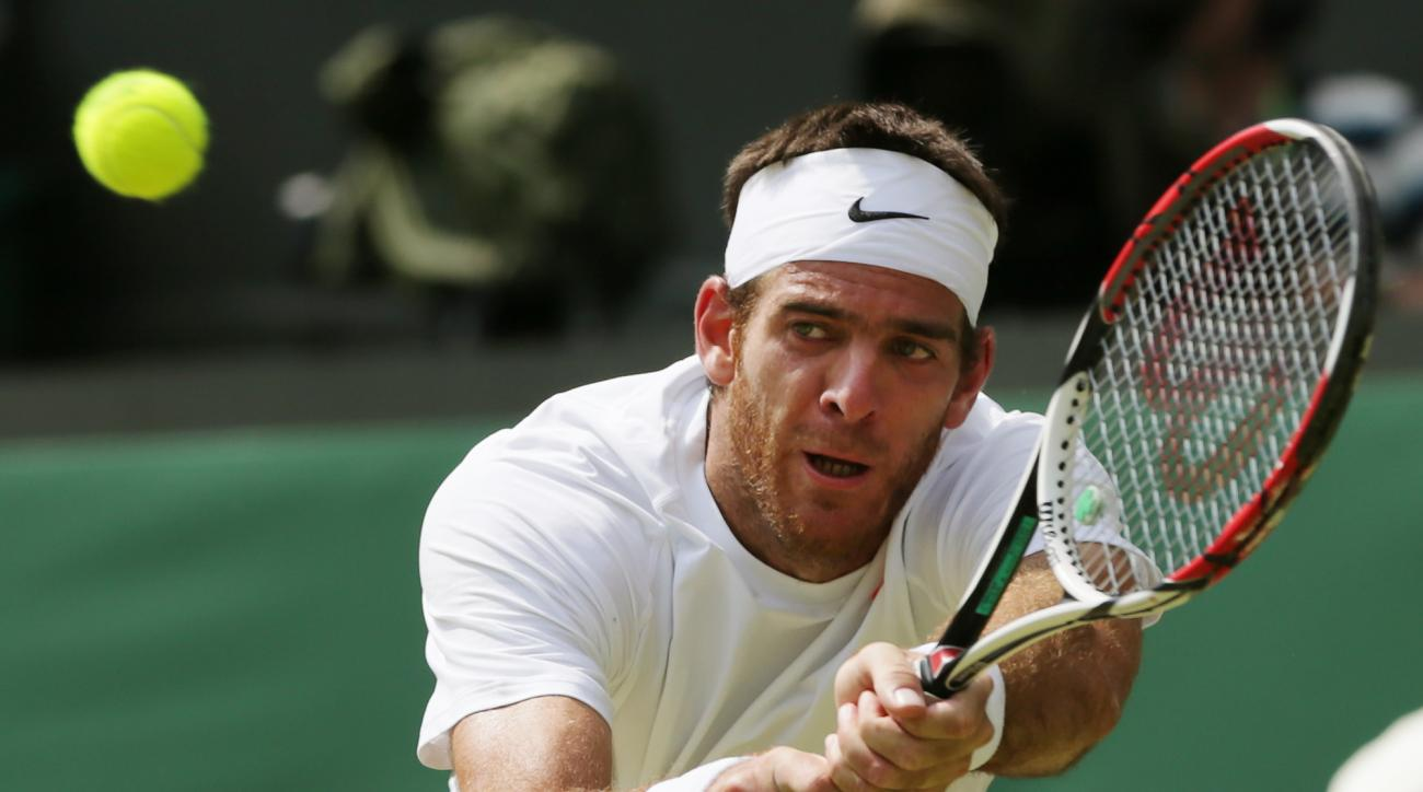 FILE- In this Friday,  July 5, 2013 file photo, Juan Martin Del Potro of Argentina returns the ball to Novak Djokovic of Serbia during their Men's singles semifinal match at the All England Lawn Tennis Championships in Wimbledon, London. Tuesday, June 28,