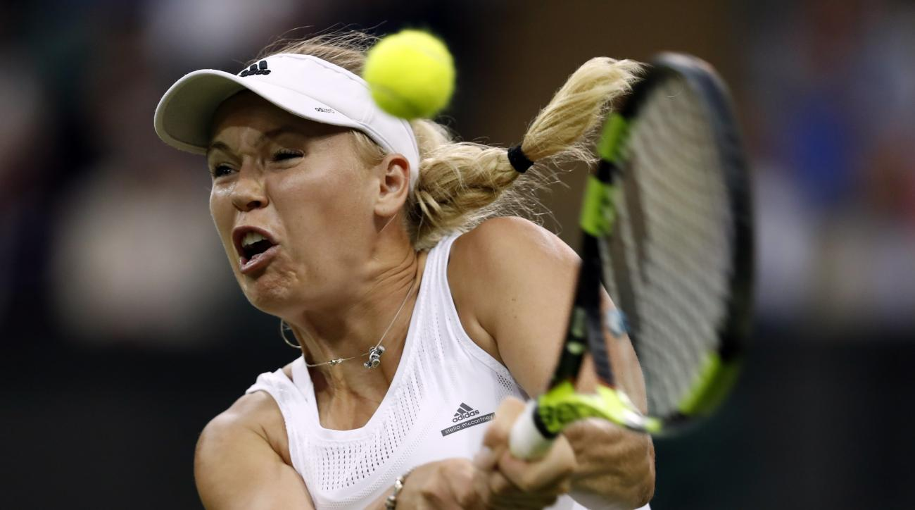 Caroline Wozniacki of Denmark returns to Svetlana Kuznetsova of Russia during their women's singles match on day two of the Wimbledon Tennis Championships in London, Tuesday, June 28, 2016. (AP Photo/Ben Curtis)