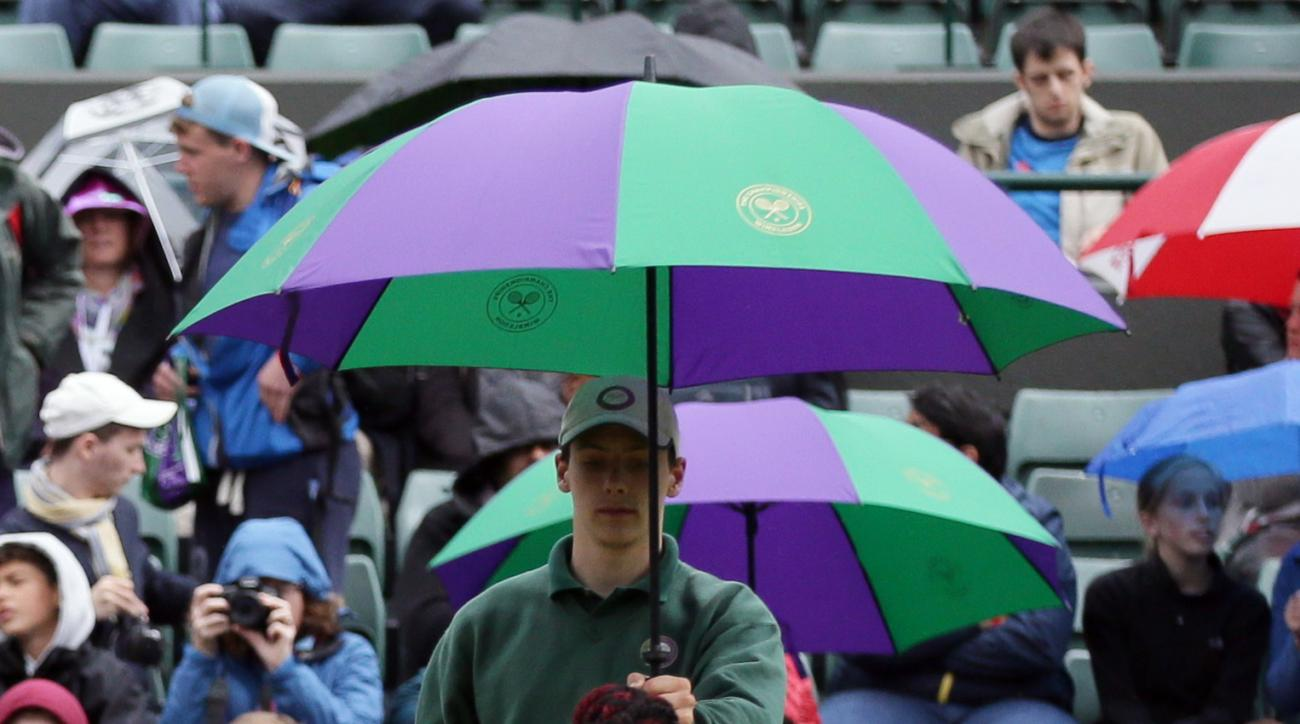 Venus Williams of the U.S takes shelter under an umbrella as rain delays her women's singles match against Daria Kasatkina of Russia on day five of the Wimbledon Tennis Championships in London, Friday, July 1, 2016. (AP Photo/Tim Ireland)