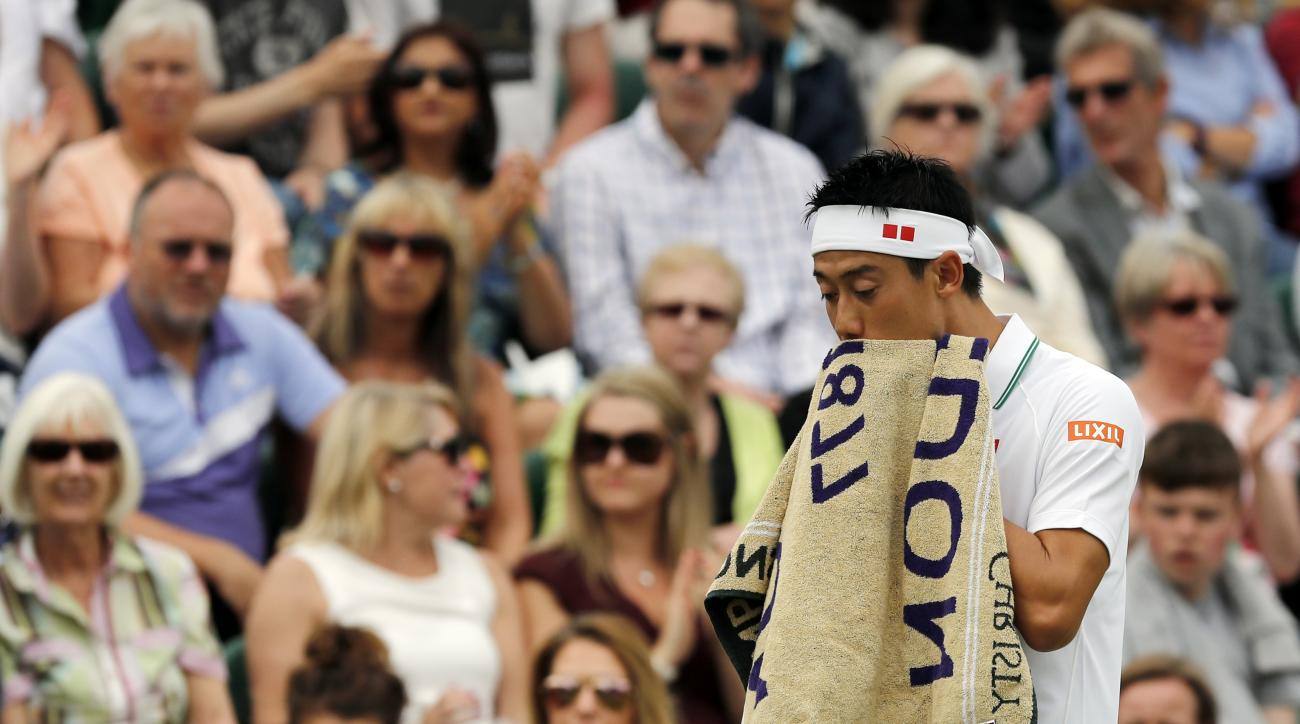 Kei Nishikori of Japan reacts before retiring injured from his men's singles match against Marin Cilic of Croatia on day eight of the Wimbledon Tennis Championships in London, Monday, July 4, 2016. (AP Photo/Ben Curtis)