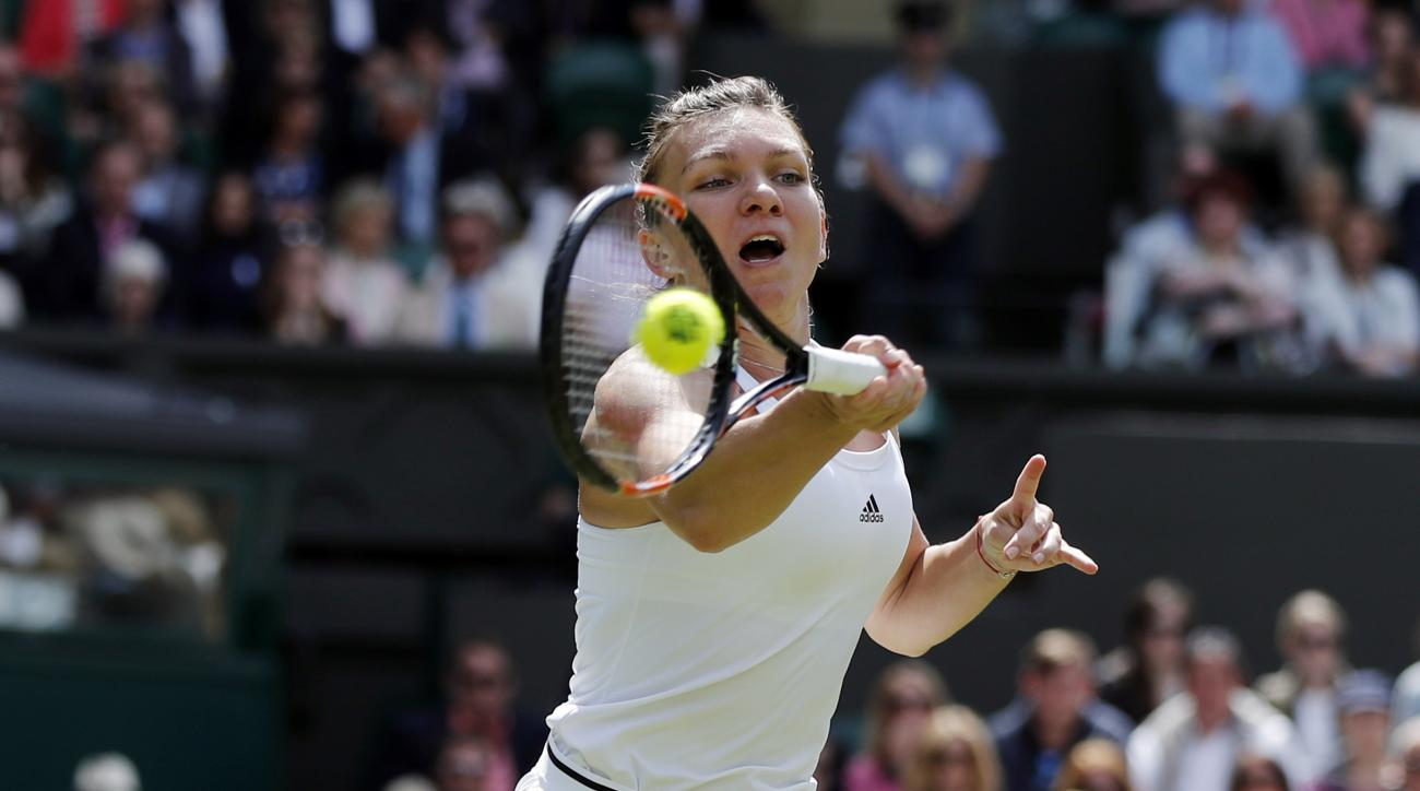 Simona Halep of Romania returns to Angelique Kerber of Germany during their women's singles match on day nine of the Wimbledon Tennis Championships in London, Tuesday, July 5, 2016. (AP Photo/Ben Curtis)