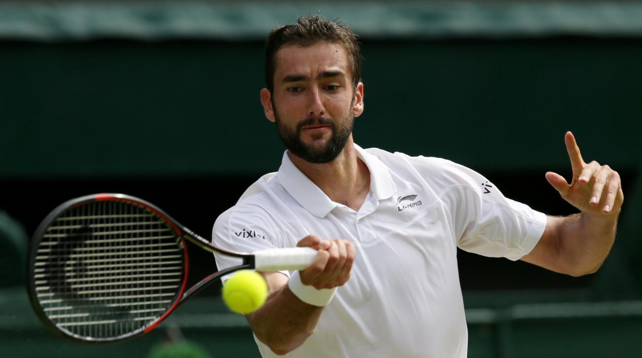 Marin Cilic of Croatia returns to Roger Federer of Switzerland during their men's singles match on day ten of the Wimbledon Tennis Championships in London, Wednesday, July 6, 2016. (AP Photo/Tim Ireland)