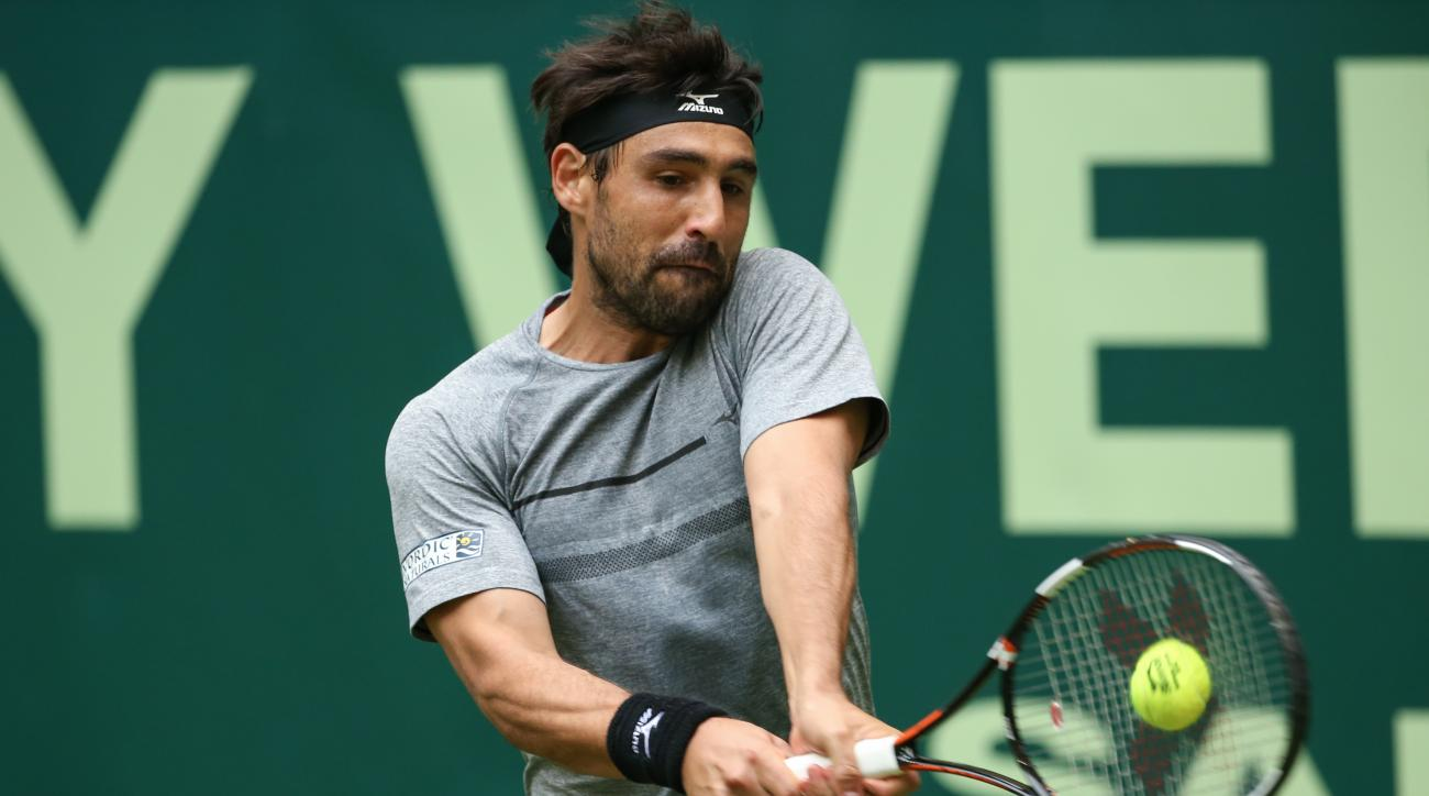 Marcos Baghdatis from Cyprus  competes  against Tomas Berdych from Czech Republic during the ATP tennis  Tournament in Halle, Germany,Tuesday June 14, 2016. (Friso Gentsch/dpa via AP)