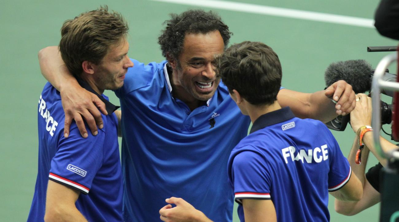 Nicolas Mahut, left, and Pierre-Hugues Herbert, right, of France celebrate with captain Yannick Noah, center, after beating Jiri Vesely and Radek Stepanek of Czech Republic during their tennis Davis Cup quarterfinal  doubles match in Trinec, Czech Republi