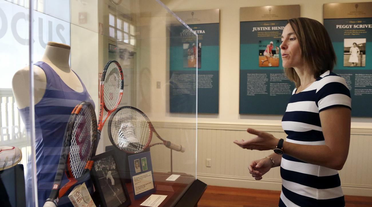 Justine Henin, of Belgium, comments on a display in the museum at the International Tennis Hall of Fame, Saturday, July 16, 2016, in Newport, R.I., prior to her induction. (AP Photo/Elise Amendola)