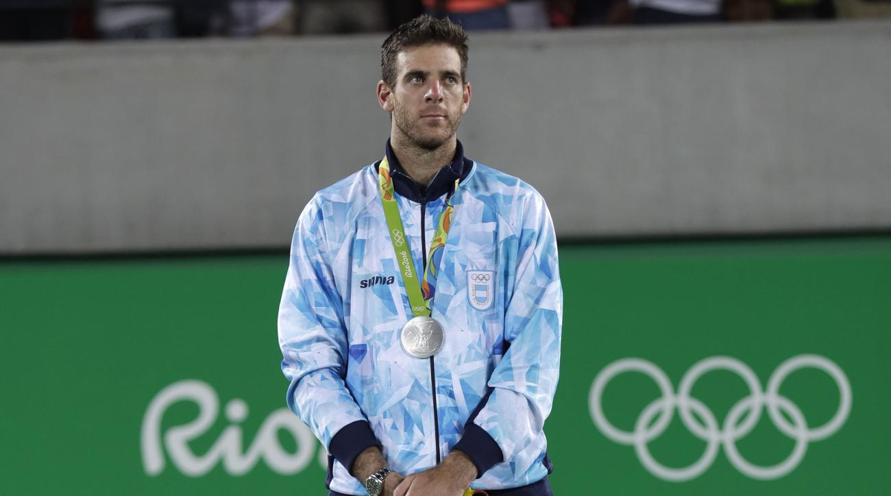 Silver medalist Juan Martin del Potro stands on the podium after the men's singles at the 2016 Summer Olympics in Rio de Janeiro, Brazil, Sunday, Aug. 14, 2016. At left is silver medalist Juan Martin del Potro. At right is bronze medalist Kei Nishikori. (