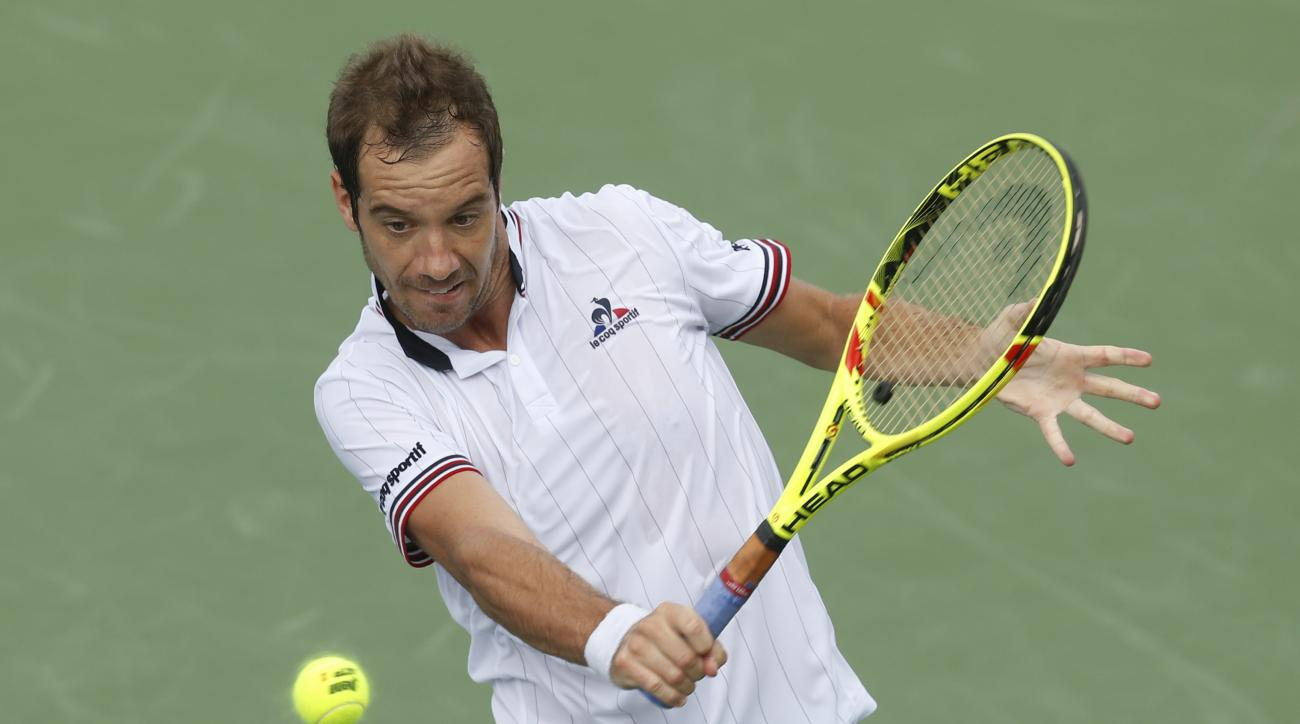 Richard Gasquet, of France, returns to Adrian Mannarino, of France, on the fourth day of the Western & Southern Open tennis tournament, Tuesday, Aug. 16, 2016, in Mason, Ohio. (AP Photo/John Minchillo)