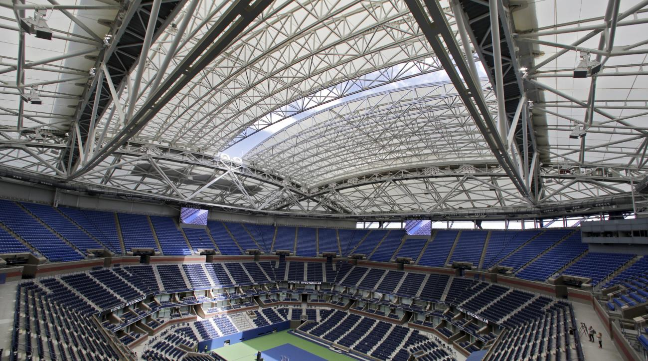 FILE - In this Aug. 2, 2016, file photo, the partially open new retractable roof allows a ribbon of light into Arthur Ashe Stadium at the Billie Jean King National Tennis Center, in the Queens borough of New York. The first round of the U.S. Open tennis t