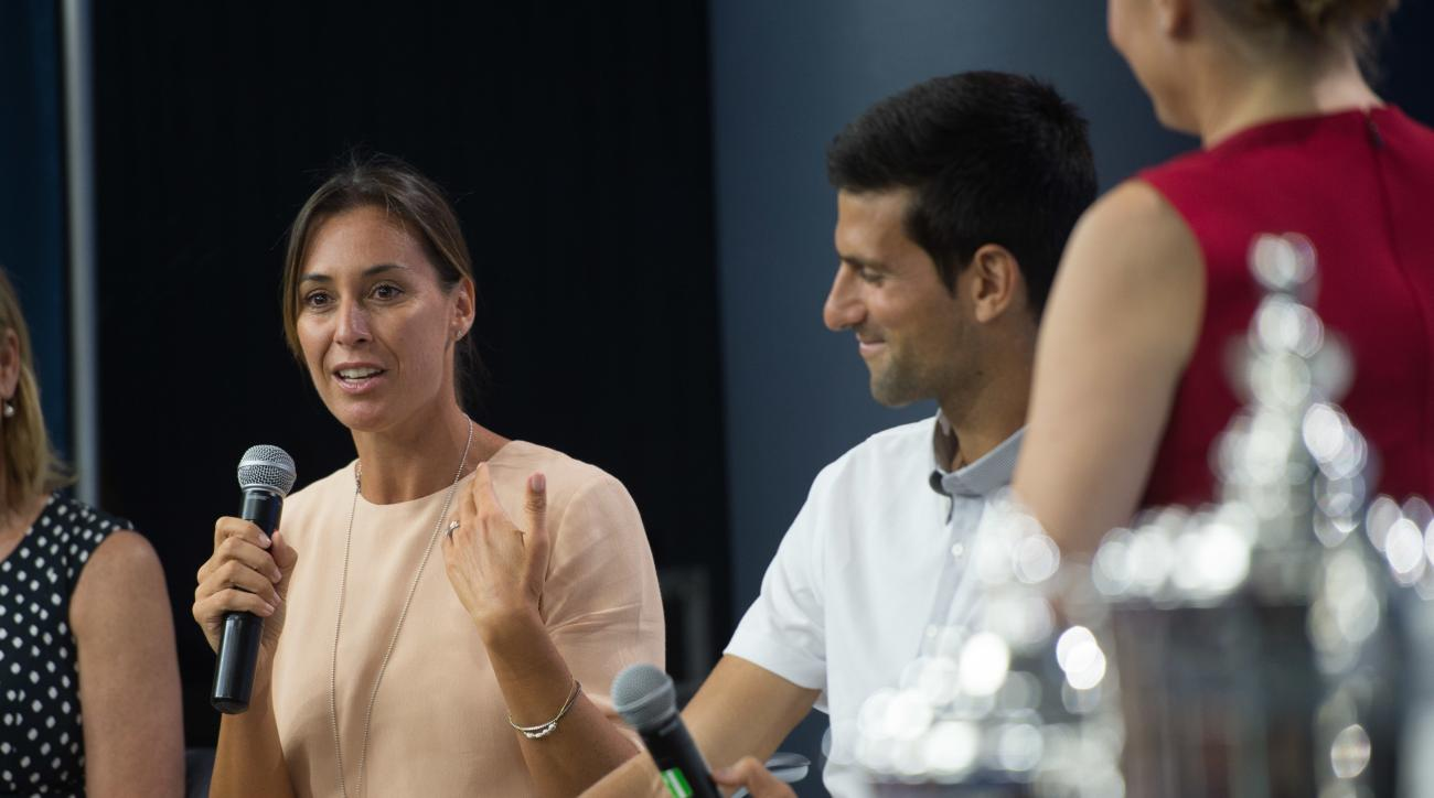 Reigning U.S. Open tennis women's singles champion Flavia Pennetta, of Italy, speaks as men's singles champion Novak Djokovic looks on during a media availability at the Billie Jean King National Tennis Center, Friday, Aug. 26, 2016,  in New York. (AP Pho
