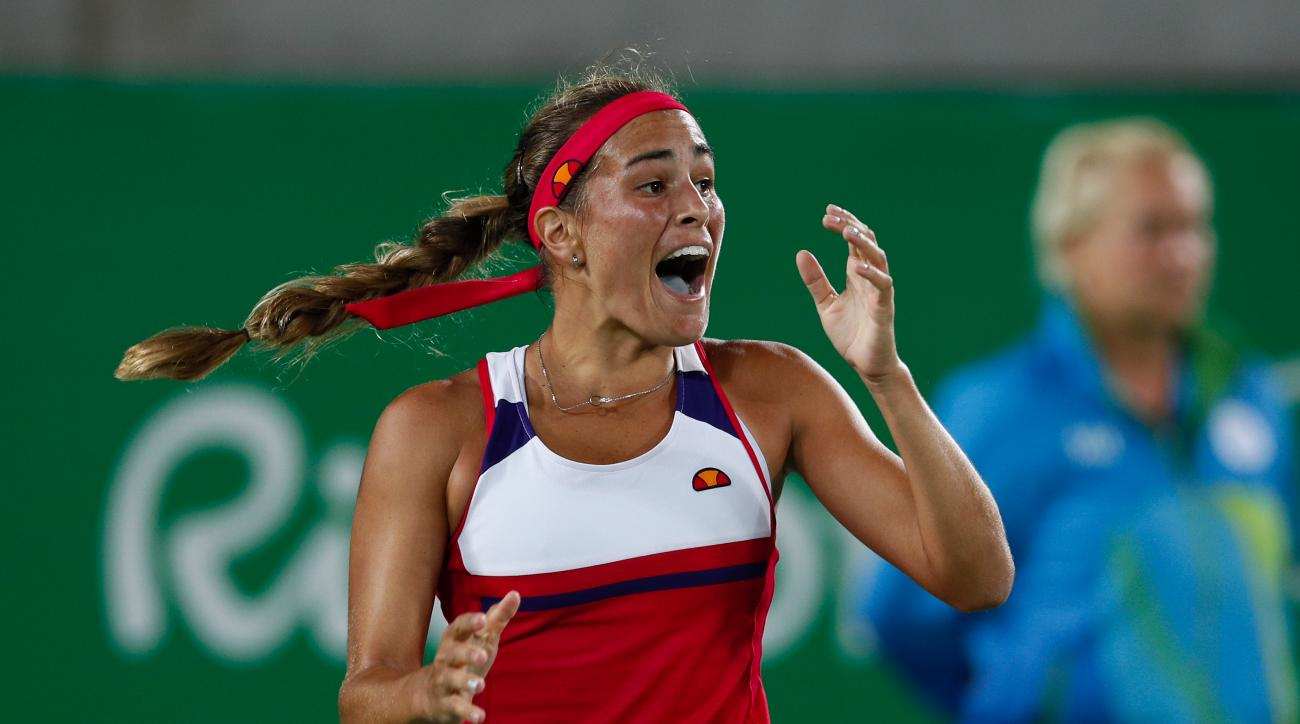 FILE- In this Aug. 13, 2016, file photo, Monica Puig, of Puerto Rico reacts after winning the final point of the gold medal match in the women's tennis competition at the 2016 Summer Olympics in Rio de Janeiro, Brazil. A few weeks ago,  Puig was a player