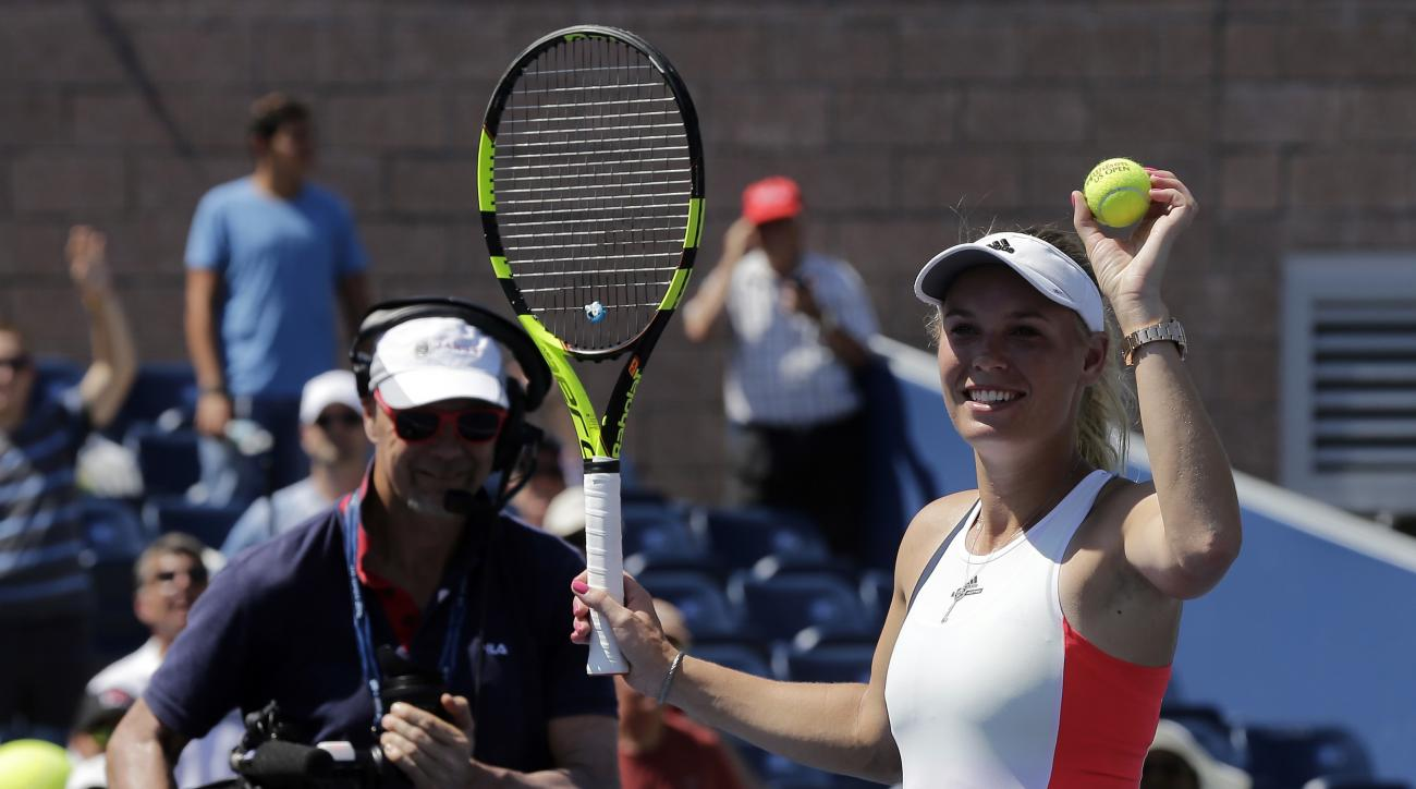 Caroline Wozniacki, of Denmark, prepares to hit balls to fans after defeating Taylor Townsend, of the United States, during the first round of the U.S. Open tennis tournament, Monday, Aug. 29, 2016, in New York. (AP Photo/Frank Franklin II)
