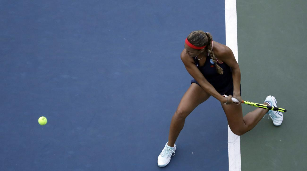 Monica Puig, of Puerto Rico, returns a shot to Zheng Saisai, of China,during the first round of the U.S. Open tennis tournament, Monday, Aug. 29, 2016, in New York. (AP Photo/Julio Cortez)