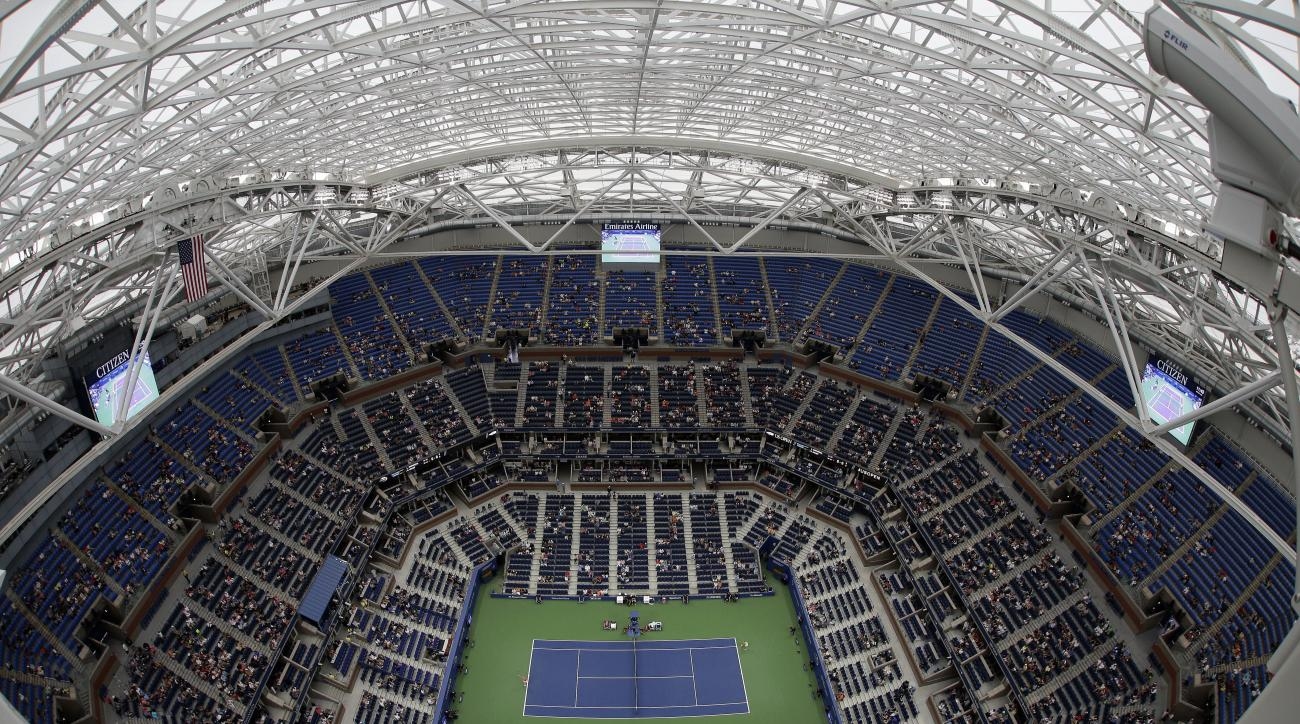 Simona Halep, of Romania, serves to Lucie Safarova, of the Czech Republic, during the second round of the U.S. Open tennis tournament, Thursday, Sept. 1, 2016, in New York. Despite rain falling outside Arthur Ashe Stadium, the new roof was closed to allow