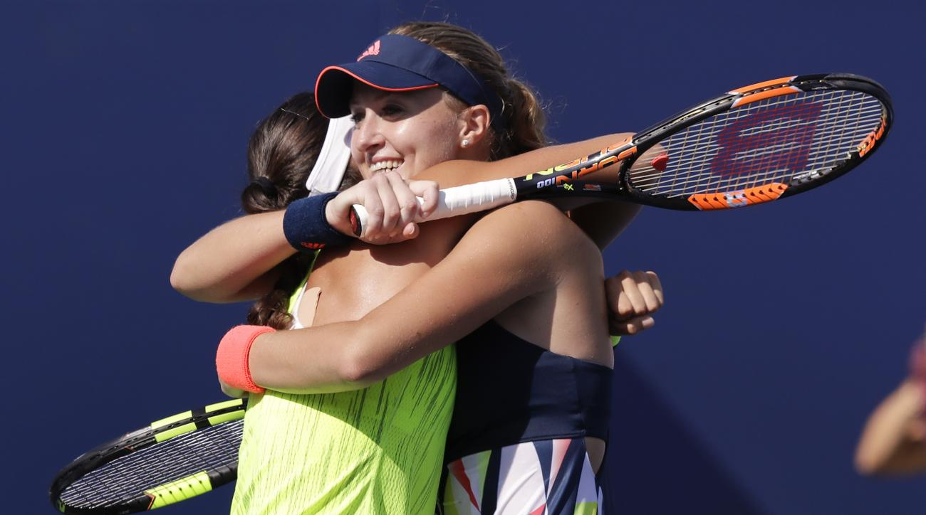 Kristina Mladenovic, of France, right, hugs doubles partner Caroline Garcia, of France, after winning their semifinal match against Martina Hingis, of Switzerland, and Coco Vandeweghe, of the United States, at the U.S. Open tennis tournament, Thursday, Se