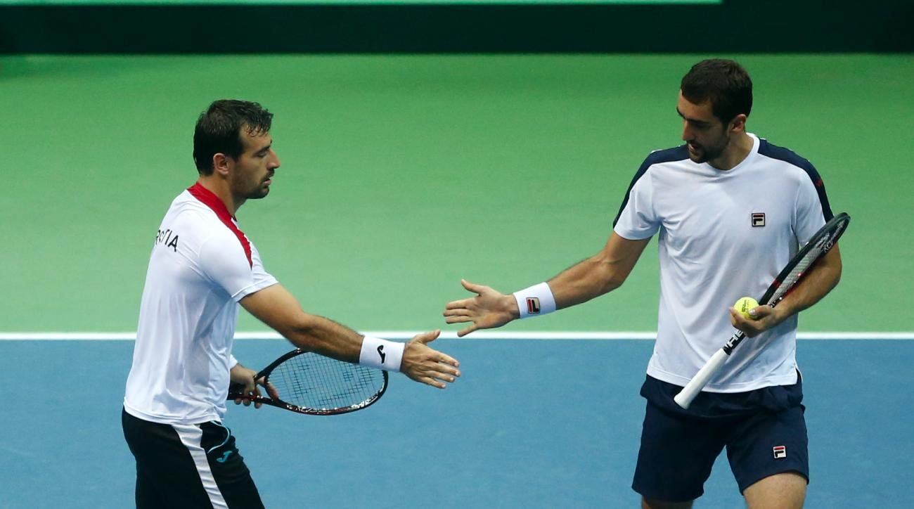 Croatia's Marin Cilic, right, and Ivan Dodig touch hands after winning a point in the doubles match against France's Pierre-Hugues Herbert and Nicolas Mahut during the Davis Cup semifinal tennis match between Croatia and France, in Zadar, Croatia, Saturda
