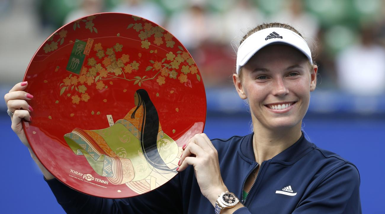 Caroline Wozniacki of Denmark poses with the winner's plate after beating Naomi Osaka of Japan at the Japan Pan Pacific Open tennis tournament in Tokyo, Sunday, Sept. 25, 2016. (AP Photo/Shizuo Kambayashi)