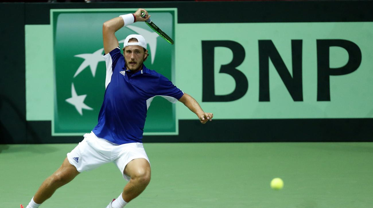 France's Lucas Pouille returns the ball to Croatia's Marin Cilic during the Davis Cup semifinal tennis match between Croatia and France, in Zadar, Croatia, Friday, Sept. 16, 2016. (AP Photo/Darko Bandic)