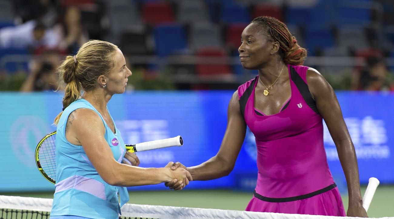 Venus Williams of the United States, right, shakes hands with Svetlana Kuznetsova of Russia after their WTA Wuhan Open in Wuhan in central China's Hubei province, Wednesday, Sept. 28, 2016. Kuznetsova defeated Williams in the match. (Chinatopix Via AP)