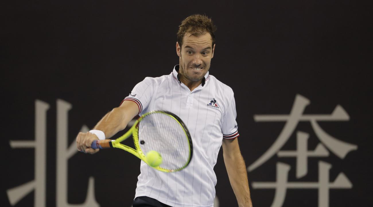 Richard Gasquet of France hits a return shot against Pablo Carreno Busta of Spain during the men's singles of the China Open tennis tournament at the Lotus Court in Beijing, Thursday, Oct. 6, 2016. (AP Photo/Andy Wong)