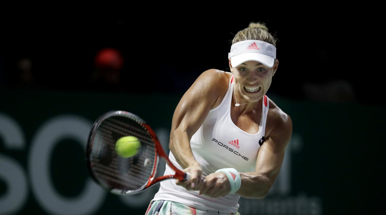 Angelique Kerber of Germany makes a backhand return against Simona Halep of Romania during their singles match at the WTA tennis tournament in Singapore, Tuesday, Oct. 25, 2016. (AP Photo/Wong Maye-E)