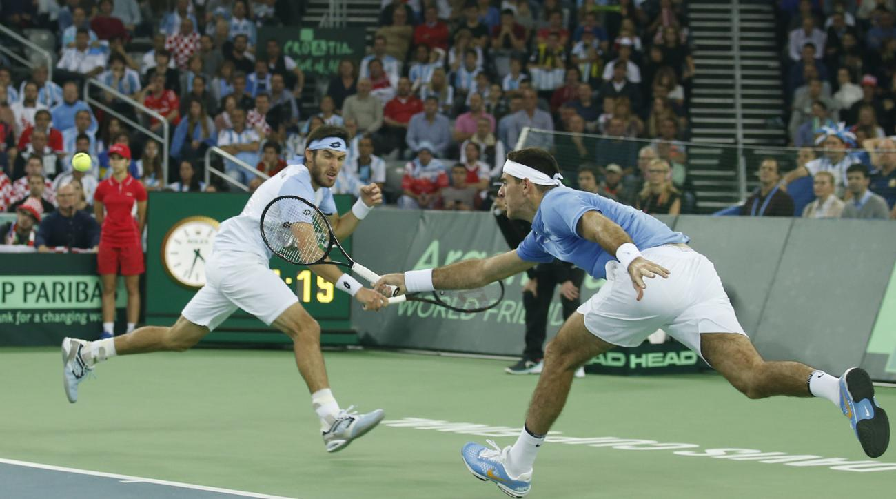 Argentina's Juan Martin Del Potro, right, and Leonardo Mayer return to Croatia's Marin Cilic and Ivan Dodig during their Davis Cup finals tennis doubles match in Zagreb, Croatia, Saturday, Nov. 26, 2016. (AP Photo/Darko Vojinovic)
