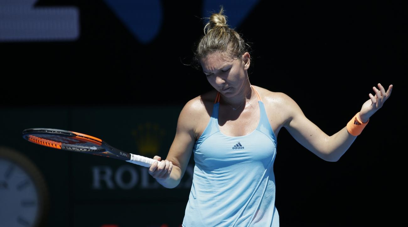 Romania's Simona Halep raise her arms after missing a shot while playing Shelby Rogers of the United States during their first round match at the Australian Open tennis championships in Melbourne, Australia, Monday, Jan. 16, 2017. (AP Photo/Aaron Favila)