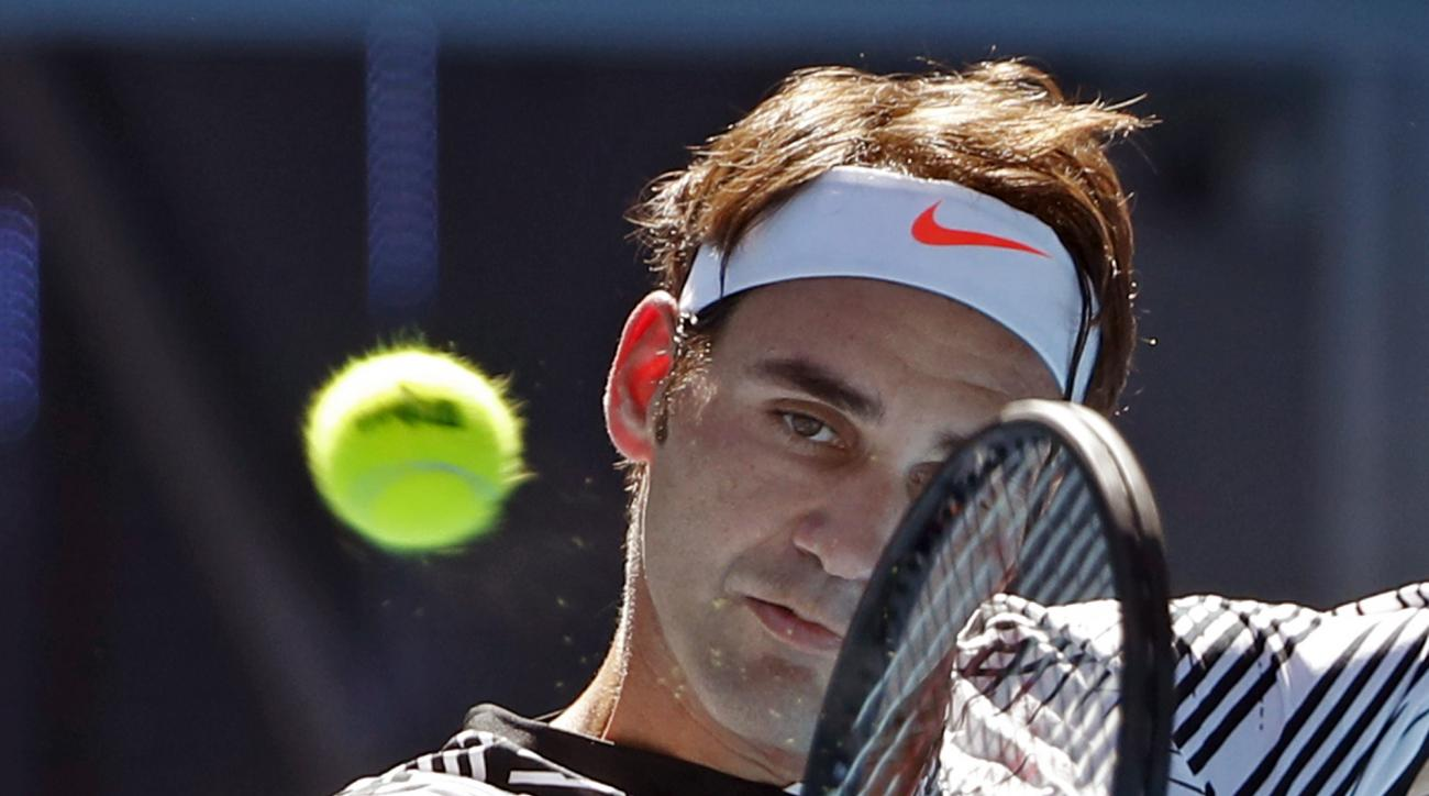 Switzerland's Roger Federer makes a backhand return to United States' Noah Rubin during their second round match at the Australian Open tennis championships in Melbourne, Australia, Wednesday, Jan. 18, 2017. (AP Photo/Dita Alangkara)
