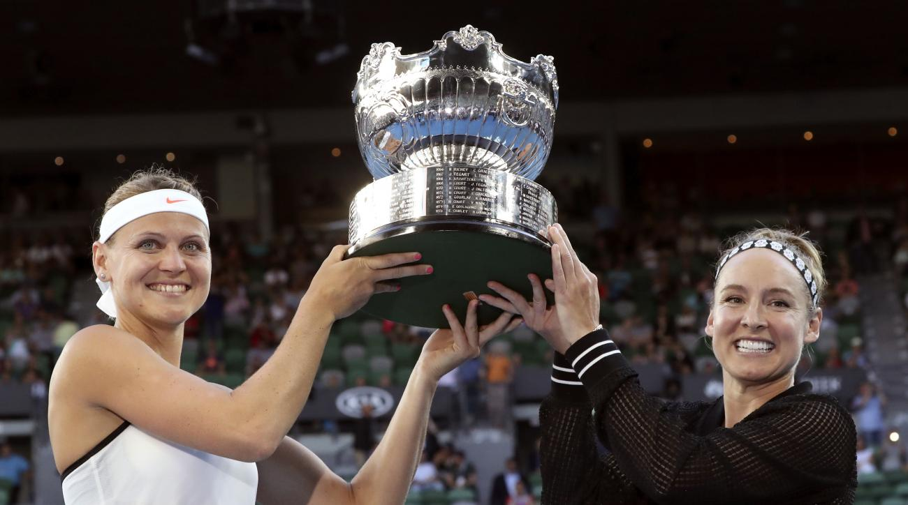 Bethanie Mattek-Sands, right, of the U.S. and Lucie Safarova of the Czech Republic hold their trophy aloft after defeating Andrea Hlavackova of the Czech Republic and Peng Shuai of China in the women's doubles final at the Australian Open tennis champions