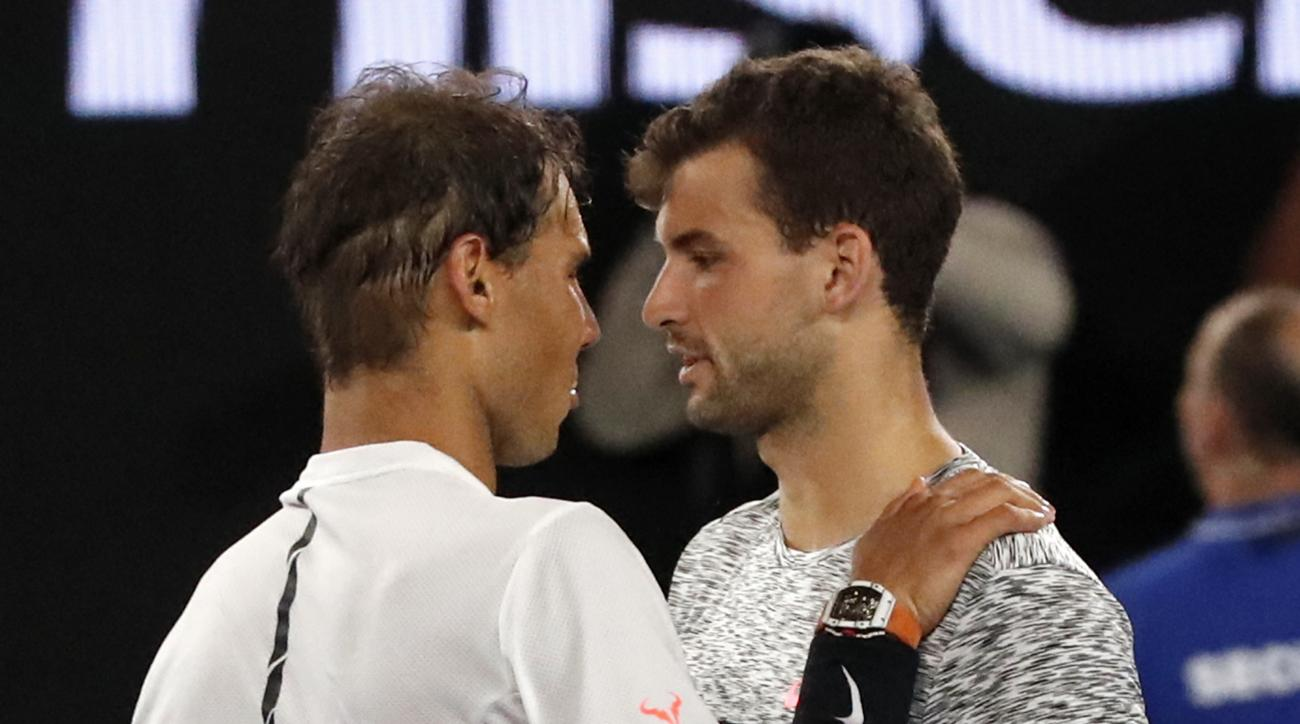 Spain's Rafael Nadal, left, is congratulated by Bulgaria's Grigor Dimitrov, after winning their semifinal at the Australian Open tennis championships in Melbourne, Australia, early Saturday, Jan. 28, 2017. (AP Photo/Dita Alangkara)