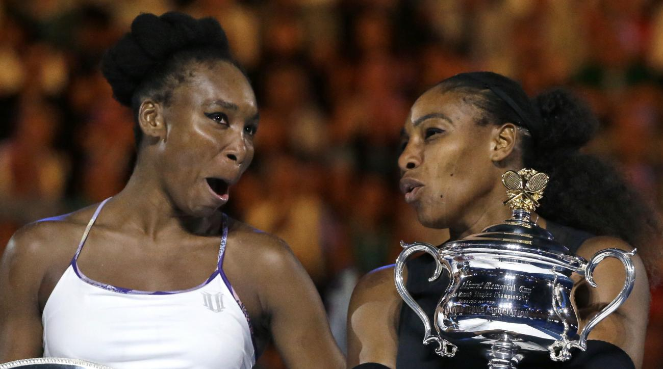 United States' Serena Williams, right, and her sister, Venus, chat, holding their trophies after Serena won the women's singles final at the Australian Open tennis championships in Melbourne, Australia, Saturday, Jan. 28, 2017. (AP Photo/Aaron Favila)